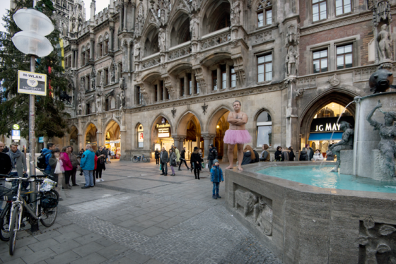 Hier posiert Bob Carey im rosa Tutu auf dem Rand des Fischbrunnens vor dem Rathaus in München.